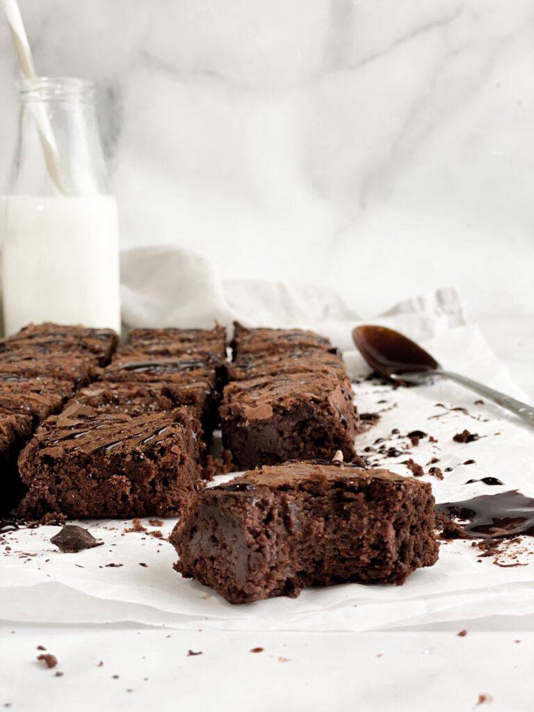 Grain-free brownies fresh out of the oven, drizzled with chocolate ganache sitting on parchment paper next to a glass of cold milk with a bite already taken out.