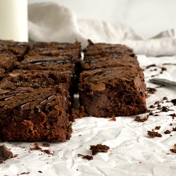 Grain-free brownies laying on parchment paper looking to cut pieces showing the chewy fudge texture in the middle of the brownies.