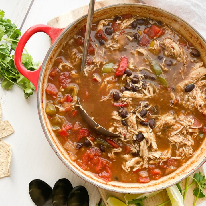 Chicken tortilla soup sitting in a small red le creuset dutch oven with a soup spoon holding a heaping portion. There are limes, cilantro and siete brand grain-free tortilla chips ready to dig in.