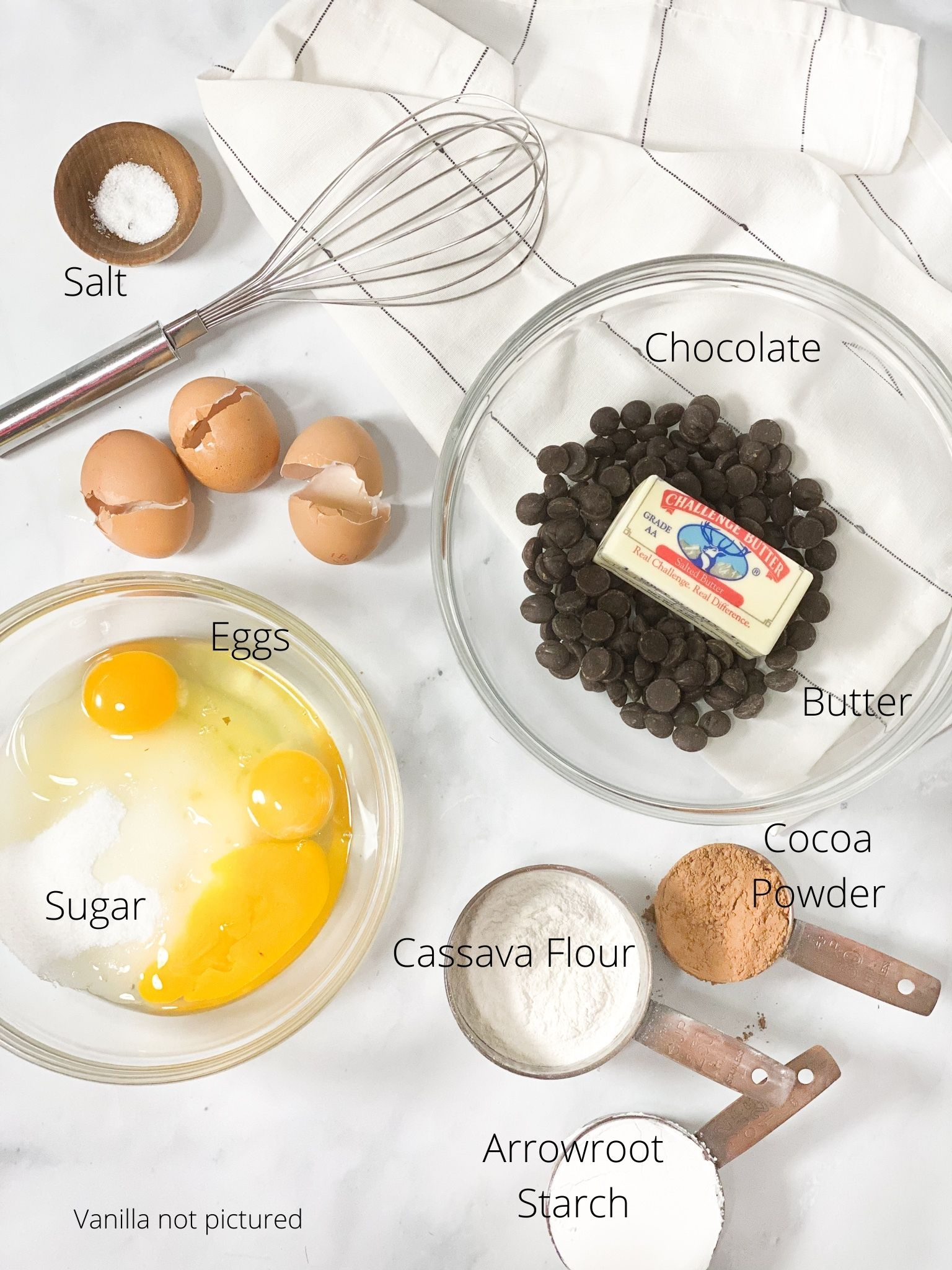 Ingredients in chewy fudge brownies. Salt in a small wooden bowl. Three cracked eggs with the sugar in a small bowl. Chocolate chips and butter in a separate bowl ready to be melted. Cocoa powder, cassava flour and arrowroot starch in copper measuring cups on the side and a whisk ready to mix it all together.