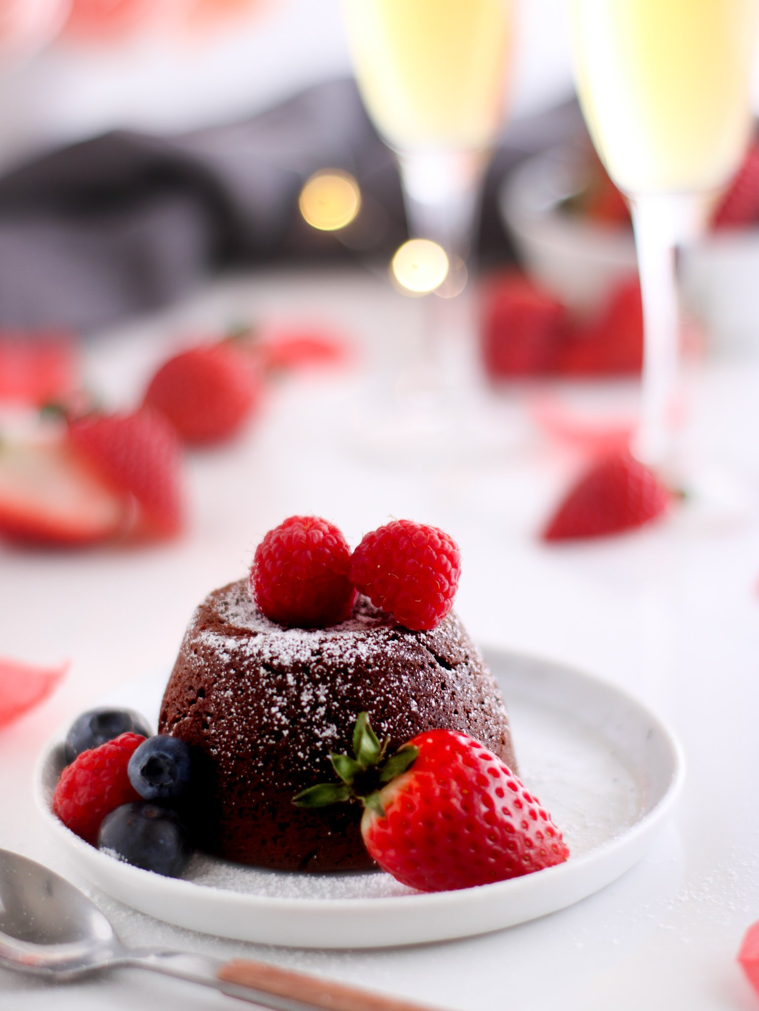 Gluten-free chocolate molten lava cake sitting on a white plate surrounded by fresh strawberries, raspberries and blueberries with two glasses of champagne in the background.
