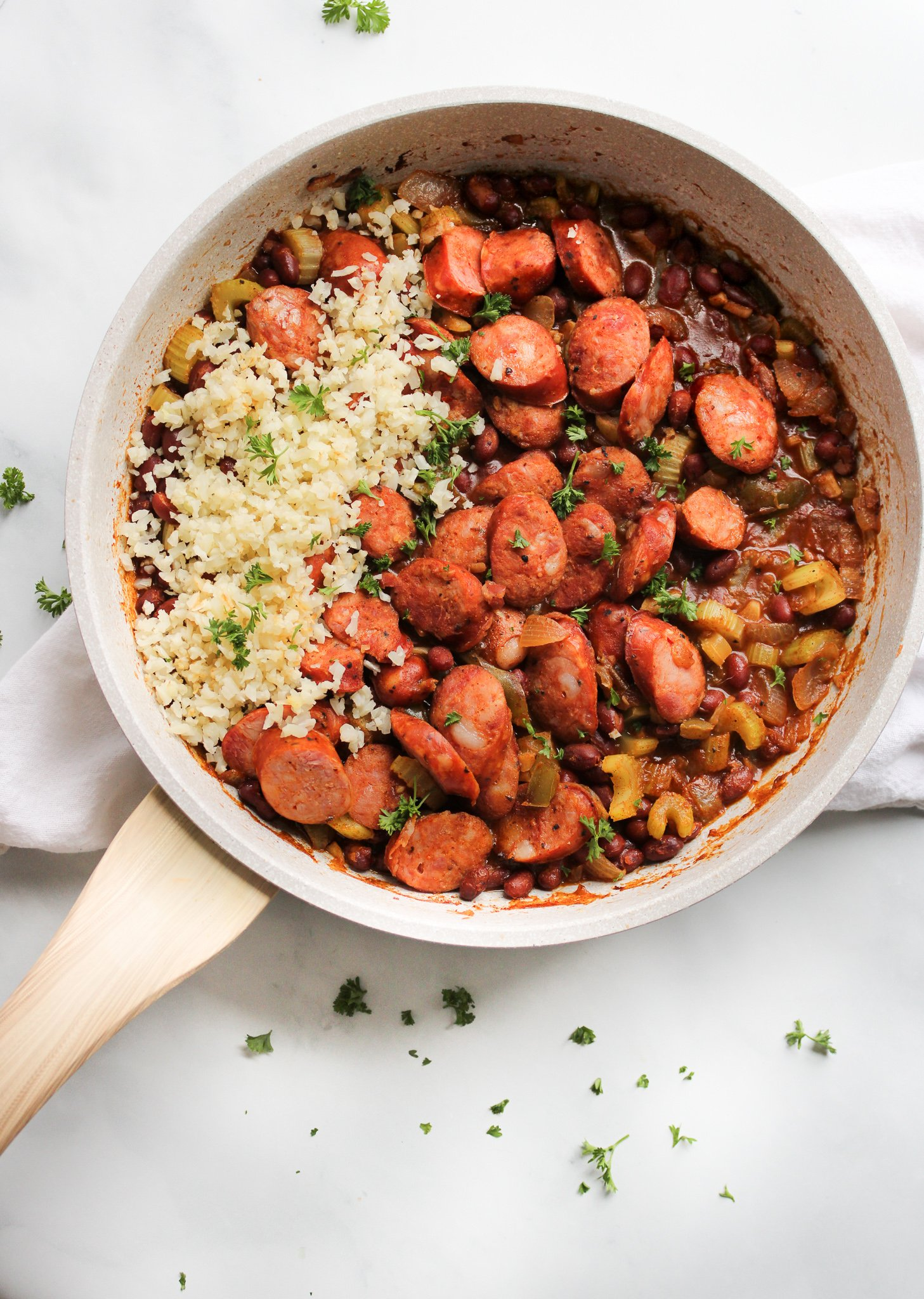 Louisiana style red beans and cauliflower rice in a white pan with a wooden handle sitting over a white table linen on a marble counter.