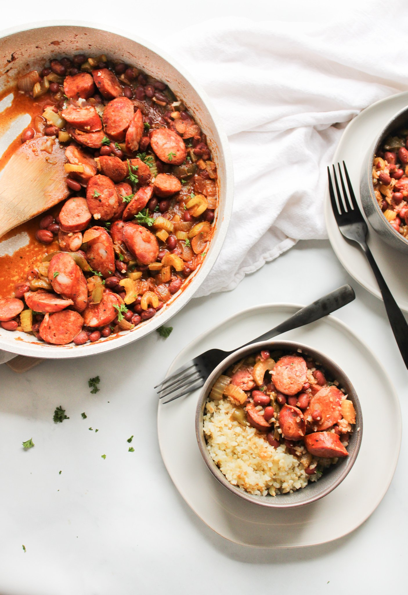 Louisiana red beans and cauliflower rice being served from a white skillet into dark grey bowls over cream colored plates and black forks.