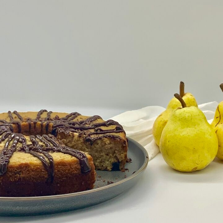 chocolate pear cardamom cake on a grey plate with a slice missing and fresh pears off to the side.