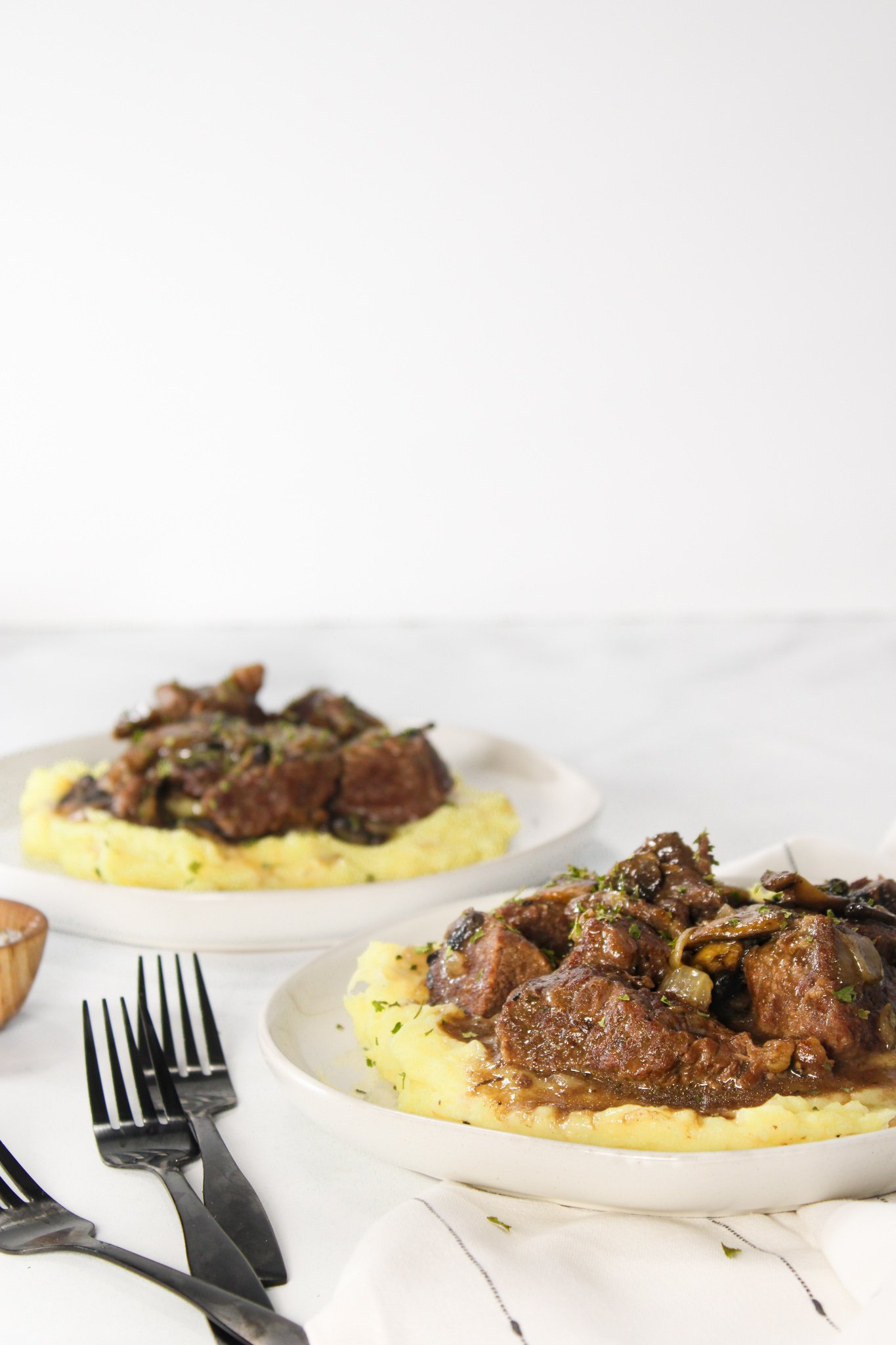Beef Tips and Gravy sitting on a cream plate in a bed of mashed potatoes topped with mushrooms, onions and gravy with some fresh parsley on top. There are two plates and the closer on is sitting on a white and black stripped napkin with black forks ready to be picked up to dig in.