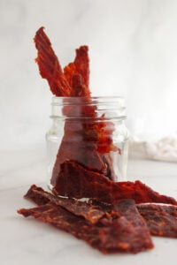 Homemade gluten-free sweet and tangy bbq beef jerky sitting in a jar and spilled over the side.