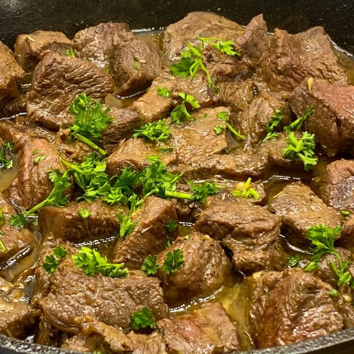 Garlic butter steak bites sitting in cast iron skillet with fresh parsley sprinkled on top.