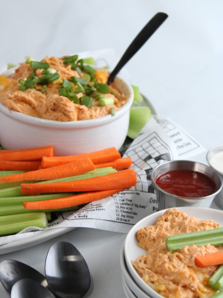 Gluten free buffalo chicken dip in a bow surrounded by sliced carrots and celery and some extra wing sauce on the side