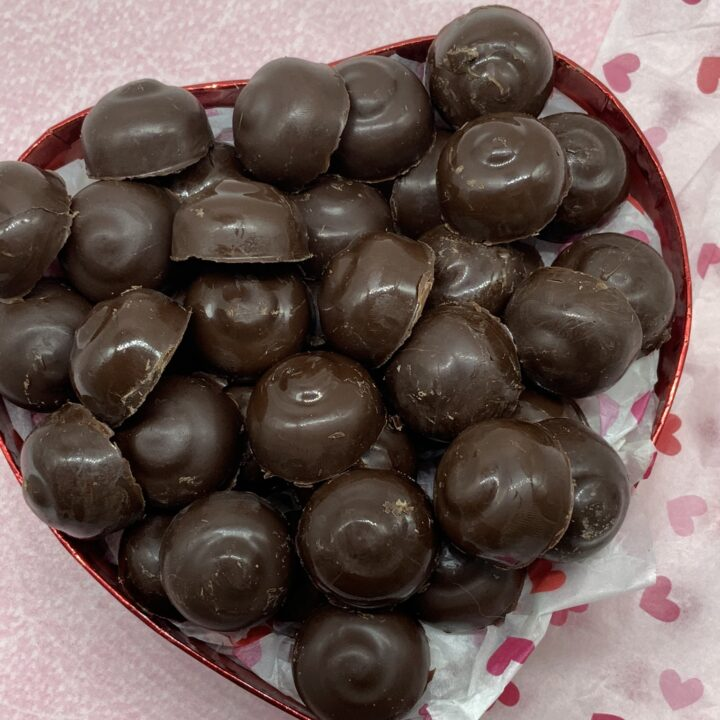 homemade chocolate caramel candies sitting in a red sparkly heart shaped box with some white tissue paper with some red hears ready to be shared and enjoyed.