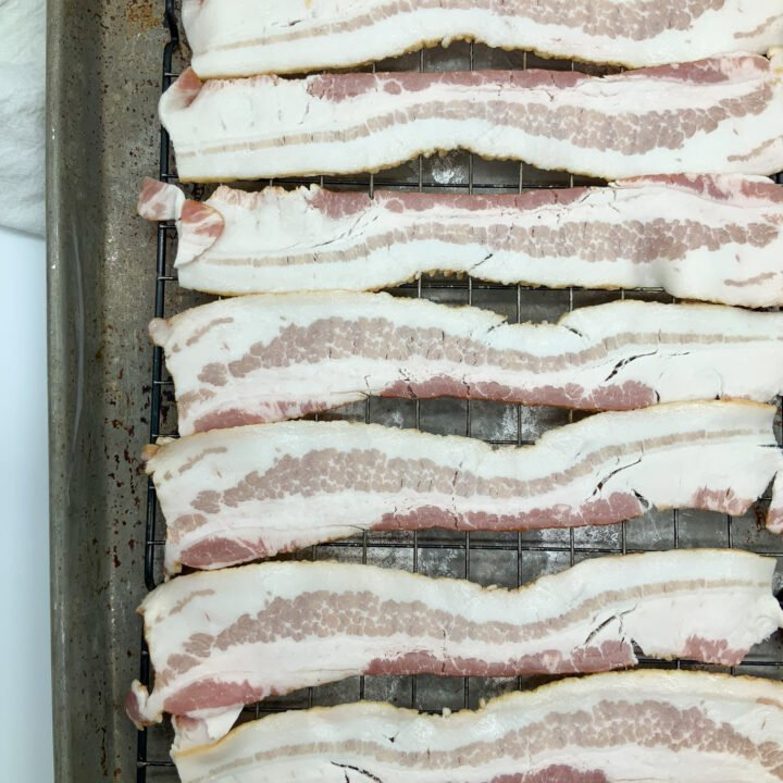 bacon on a tray layed out about to be put into the oven and baked until it's perfectly crispy