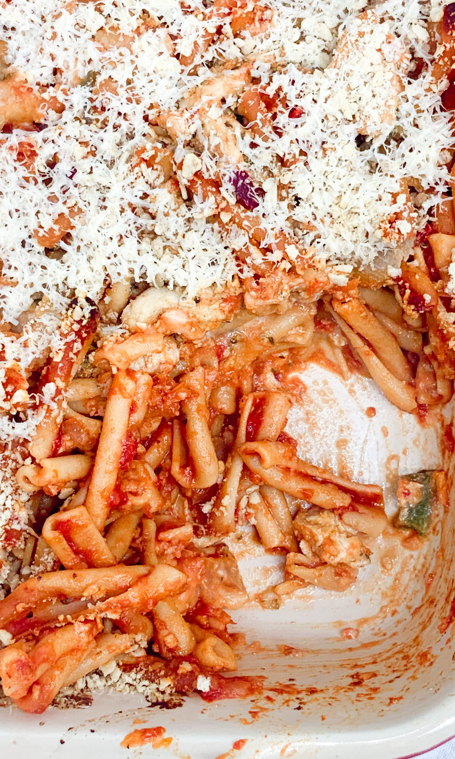 baked chicken parmesan casserole in a baking dish with a serving taken out of it showing off the textures inside the dish.