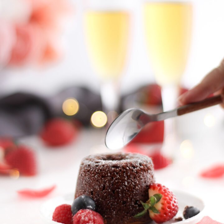 gluten free molten lava cake surrounded by fresh berries in a perfect scene for a valentines day treat for two.