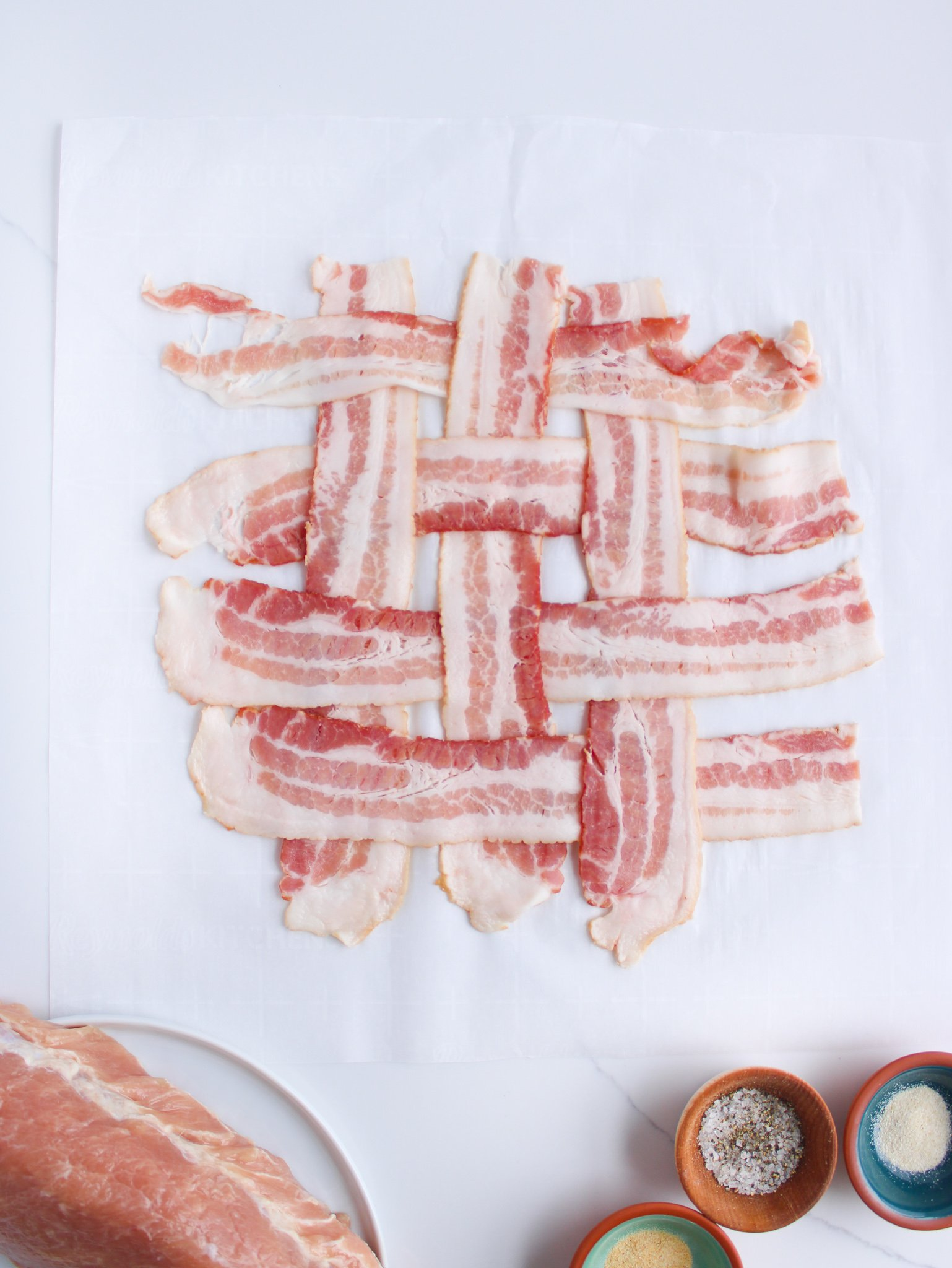 Basket weave of bacon on parchment paper about to be par cooked before being wrapped around the pork loin.