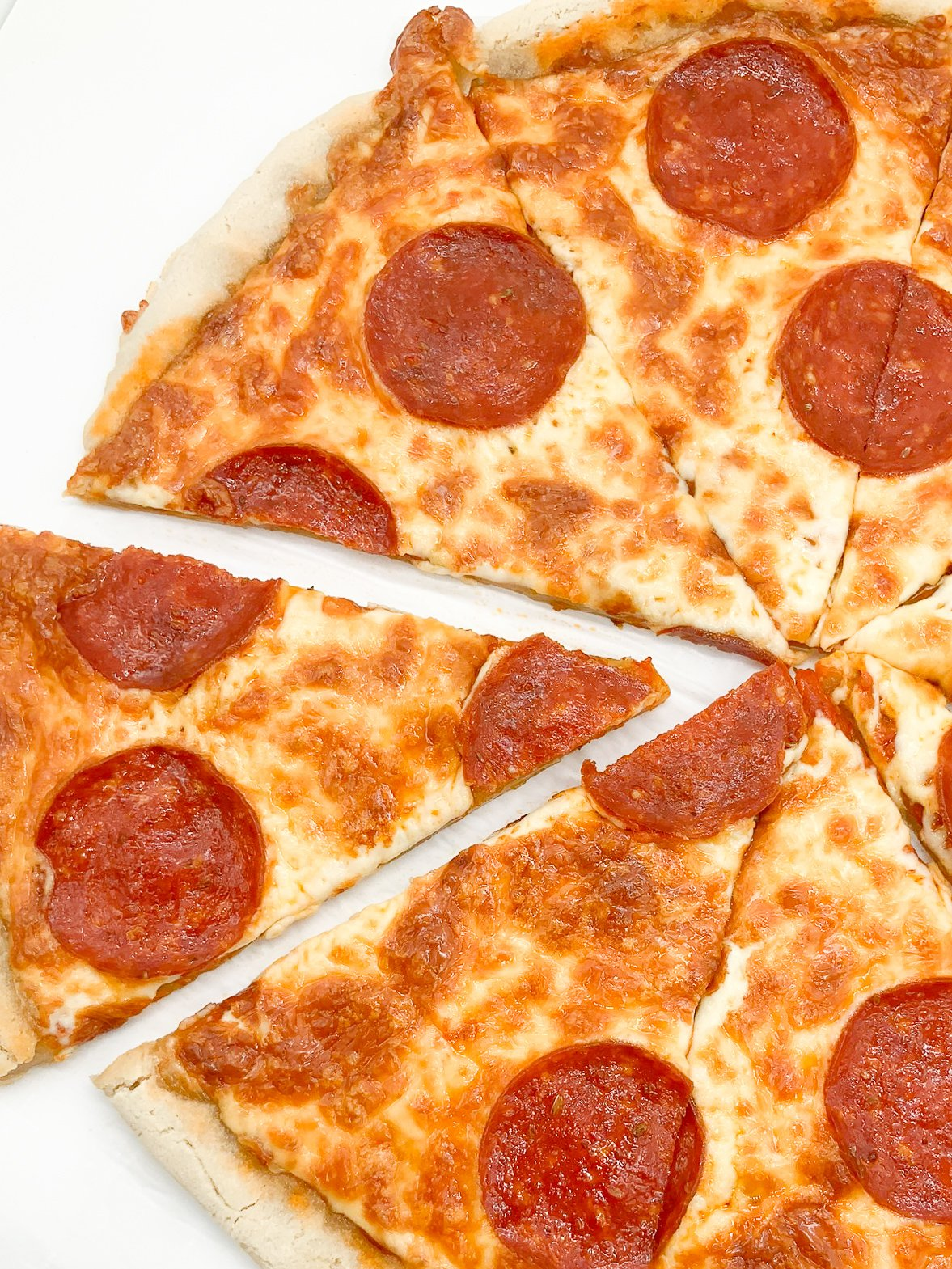 grain-free pepperoni pizza sliced and being grabbed
