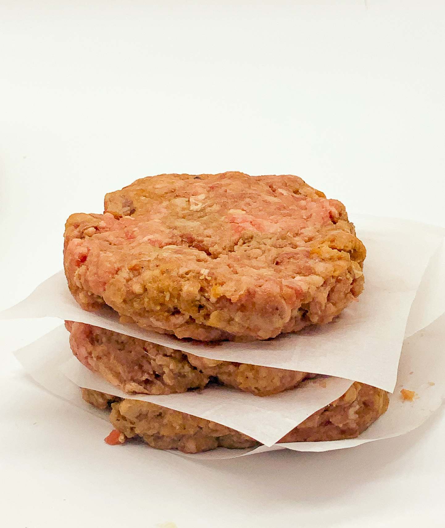 easy hamburger patties sitting in a stack separated with parchment squares