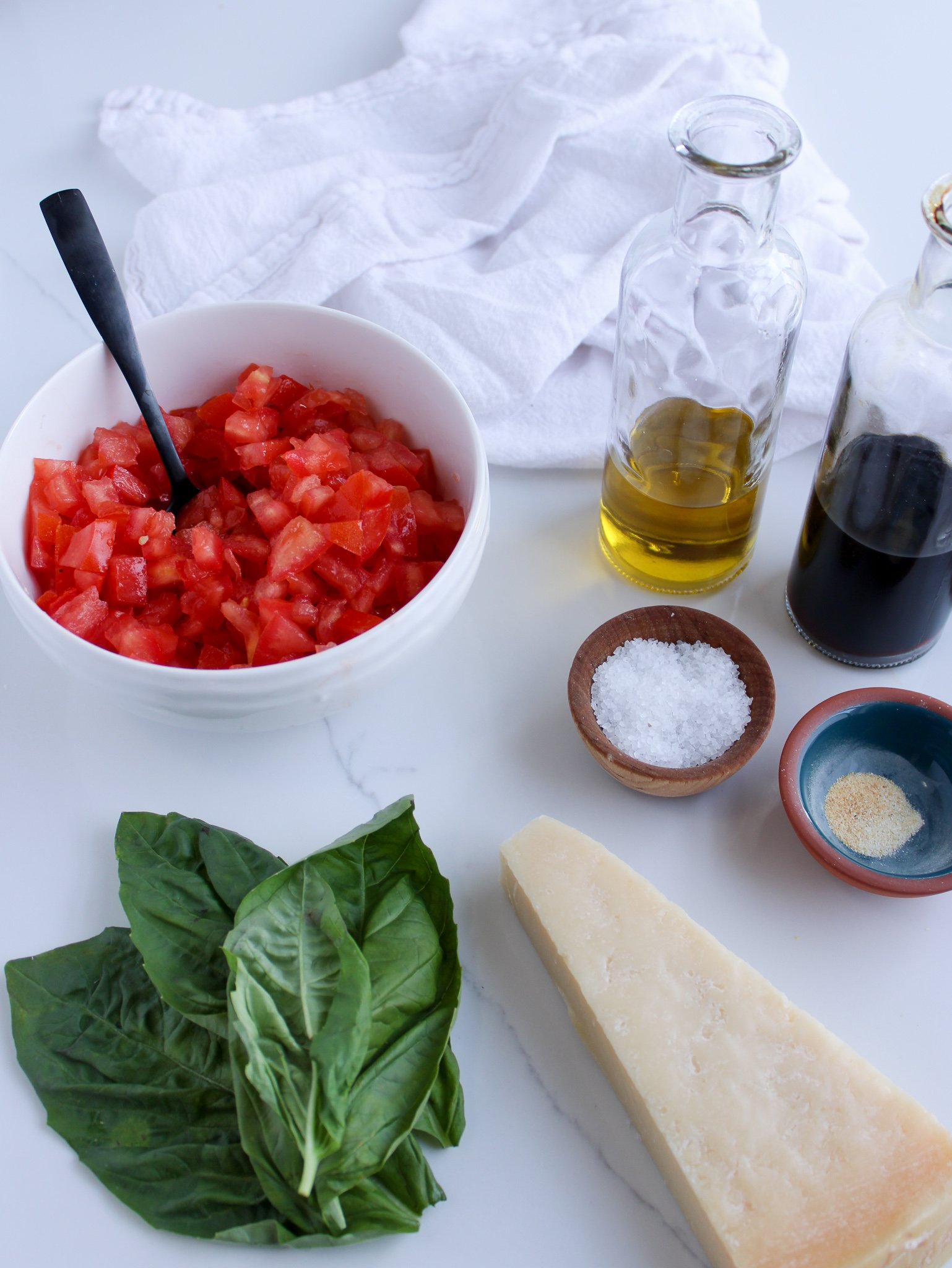 Ingredients for a classic bruschetta dip laid out including tomatoes, olive oil, balsamic vinegar, salt, garlic, fresh basil and optional parmesan cheese.