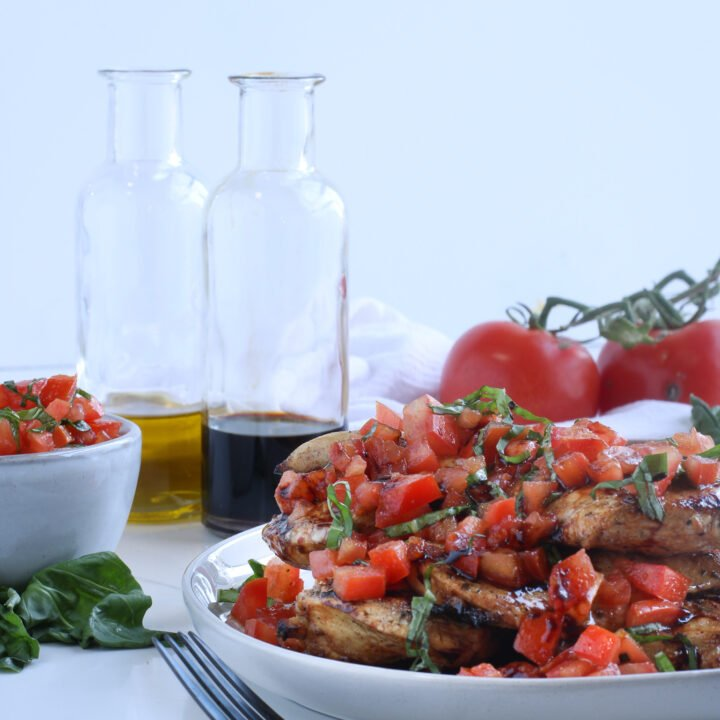 Balsamic bruschetta chicken stacked high on a white plate surrounded by more fresh ingredients and more fresh bruschetta drizzled with a balsamic glaze ready to be eaten with black silverware hot off the grill.