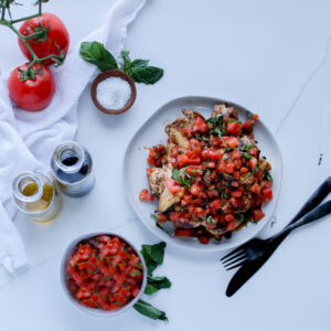 Balsamic bruschetta chicken stacked on a white plate surrounded by fresh tomatoes, basil, olive oil, balsamic vinegar and of course more freshly made bruschetta in a bow.