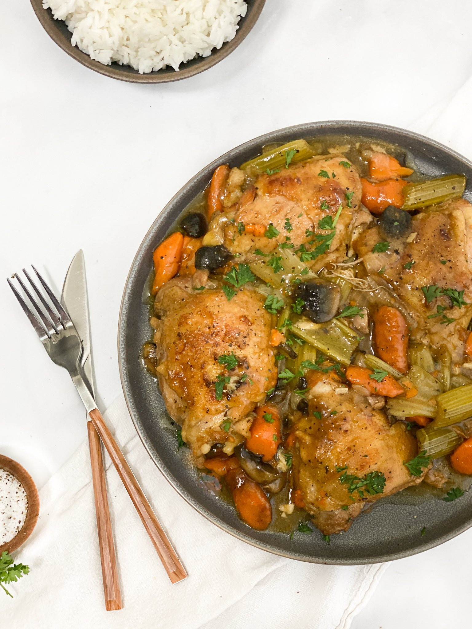 Rustic braised chicken with it's roasted veggies and pan gravy. with a bowl of jasmine rice on the side.
