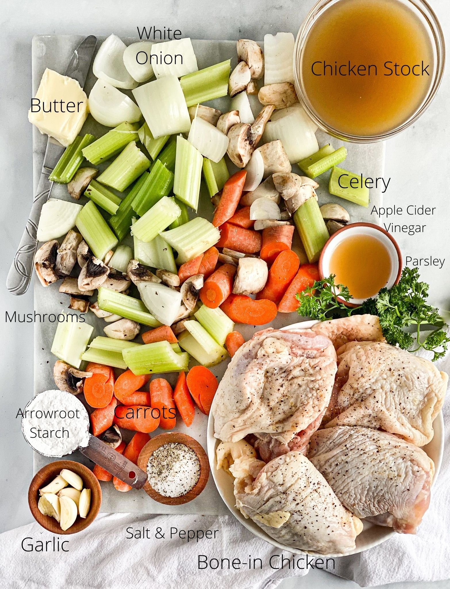 Ingredients for rustic braised chicken ready to be cooked laying on a marble cutting board which includes the following, onion, carrots, celery, mushrooms, garlic, butter, chicken stock, apple cider vinegar, butter, arrowroot, parsley salt and pepper and the bone-in chicken thighs.