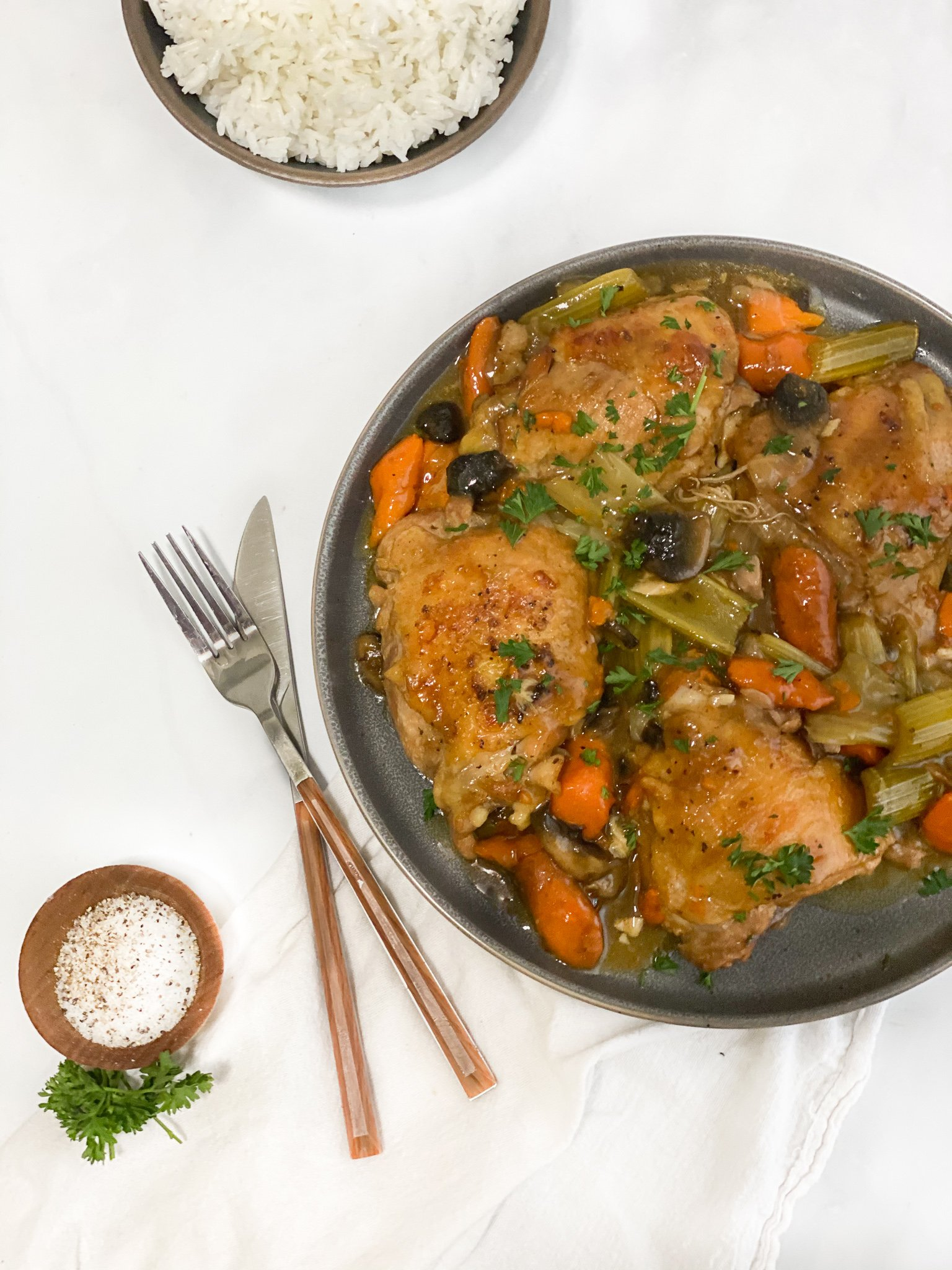 Rustic chicken thighs are sitting on a gray stone plate nestled with the roasted carrots, onions, celery and mushrooms and pan gravy. Sitting above it is a fresh bowl of jasmine rice. There is a small ramekin of salt and pepper and a knife and fork for someone to dig right in.