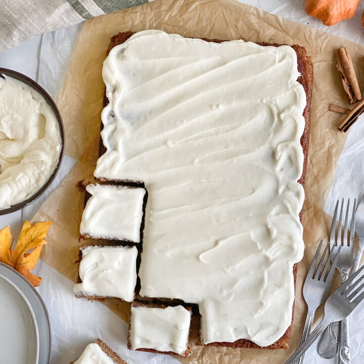 Grain-free pumpkin bars sitting next to a bowl of cream cheese frosting, small grey stacked plates, squares of slices cut out of the bottom right corner with forks, cinnamon sticks and of course, a pumpkin.