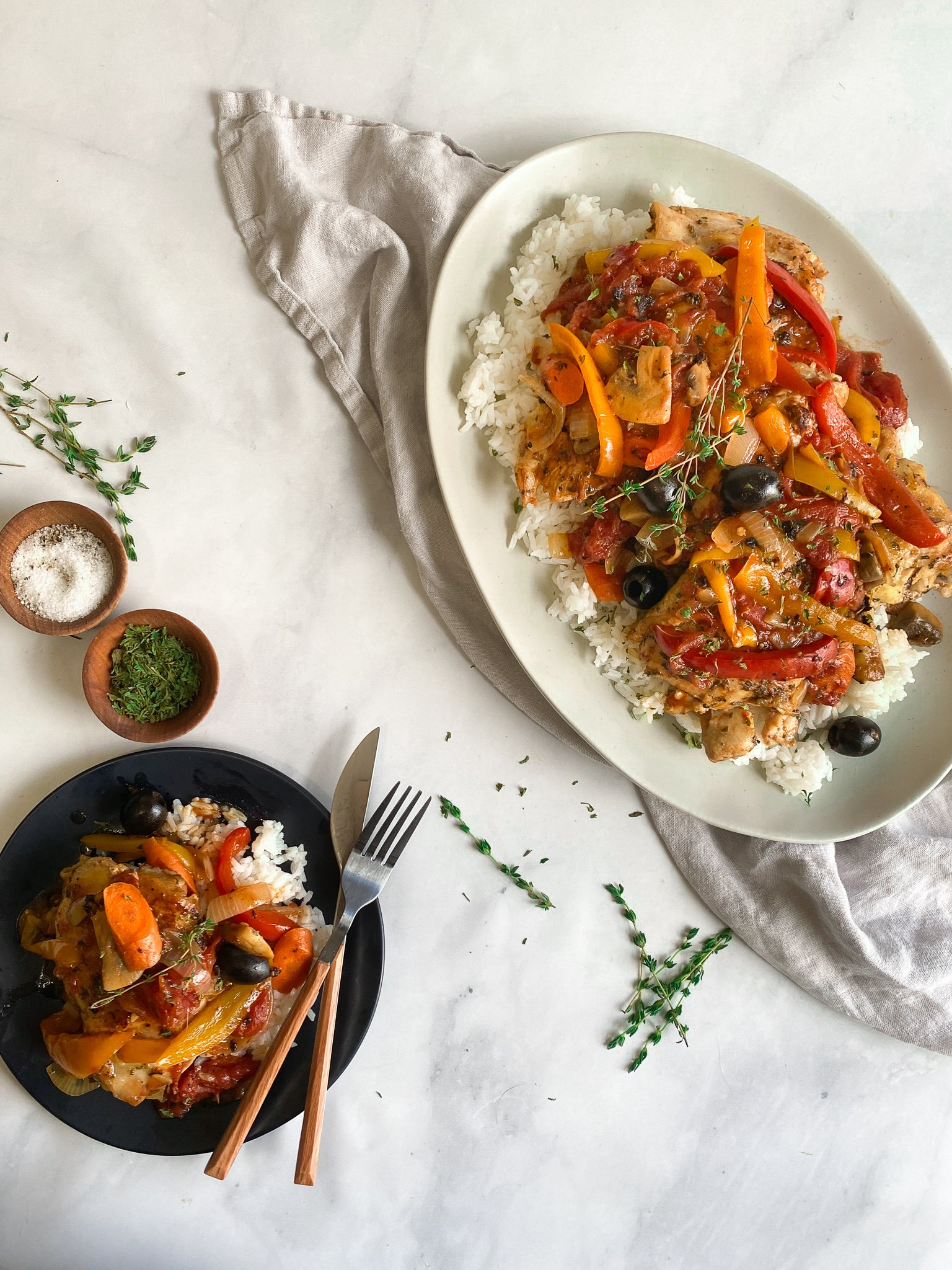 Classic chicken cacciatore with bell peppers, mushrooms, onions, carrots, garlic, Kalamata olives and crush tomatoes were simmered in together with chicken thighs until they are fall off the bone tender. They are being served over a bead of jasmine rice on a grey platter and a black plate with extra parsley on the side.