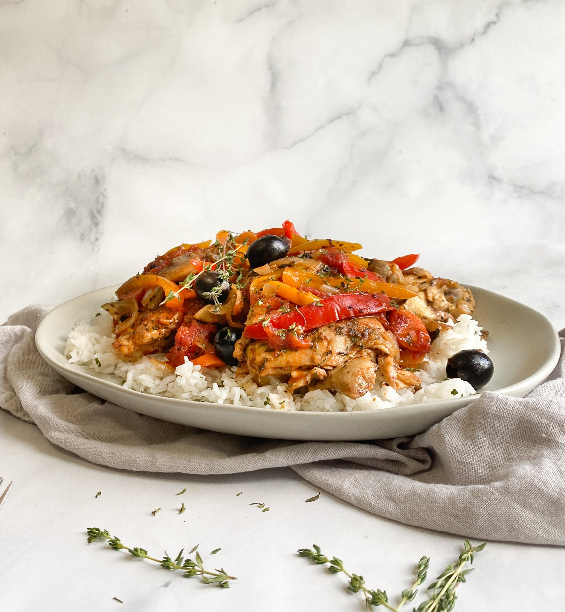 Classic chicken cacciatore sitting on top of a grey platter over a bed of jasmine rice.