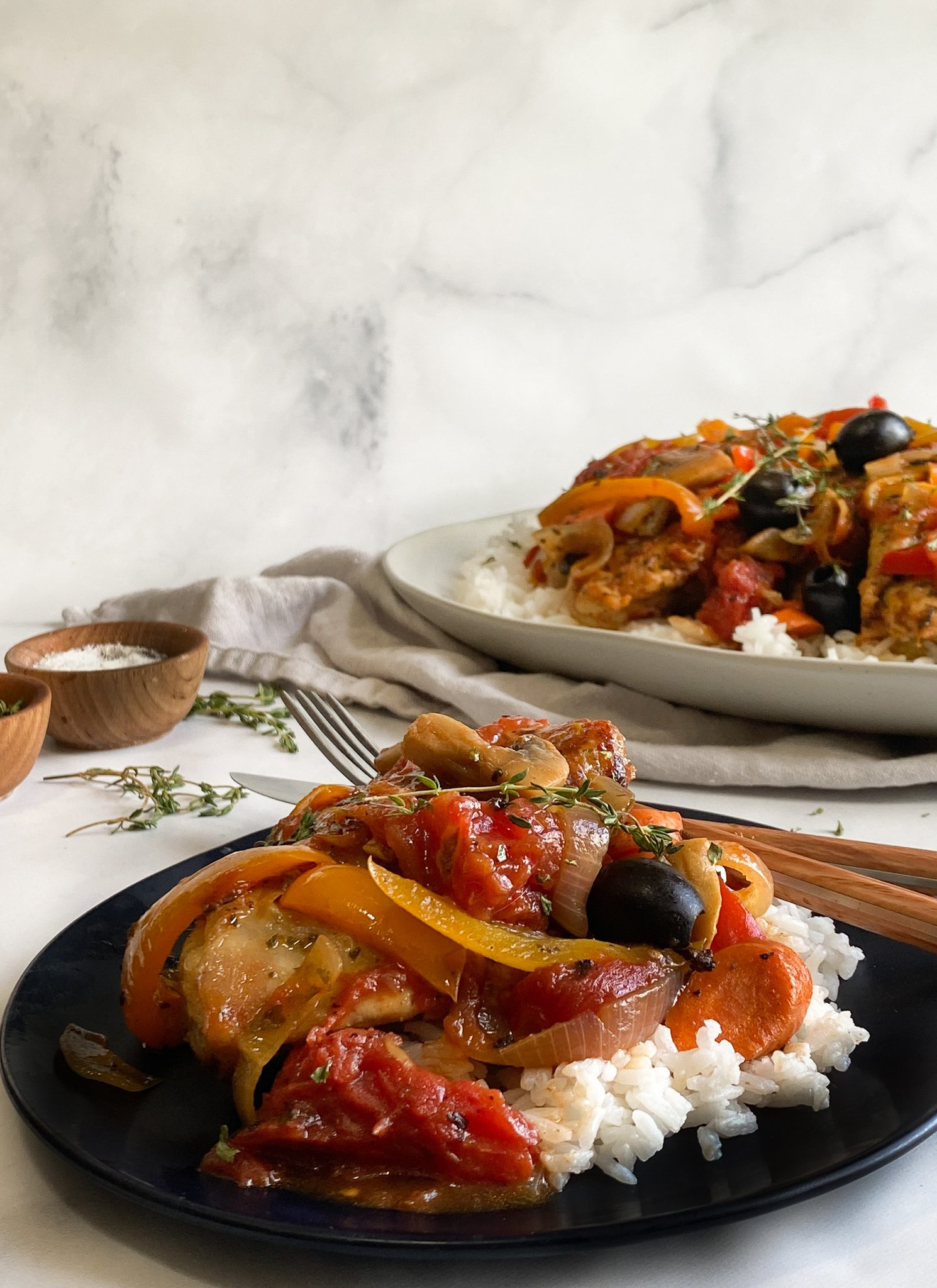 A serving of chicken cacciatore is sitting on a black plate over a bed of jasmine rice with the platter of the remaining dish in the background ready to be served up and eaten by the entire family.