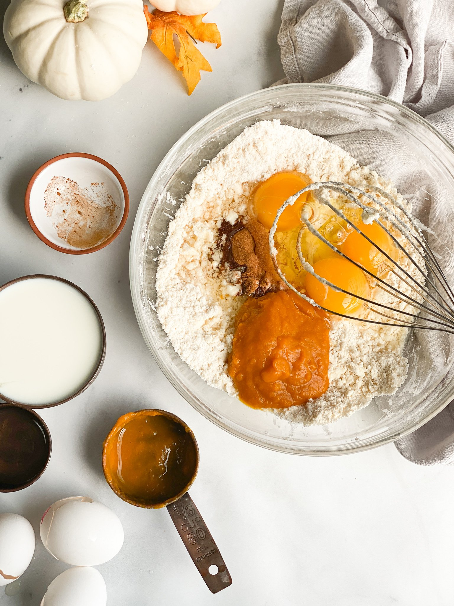 Step 2 of pumpkin waffles is to whisk in the eggs, pumpkin puree, spices, and avocado oil into the flour and butter and flour mixture.