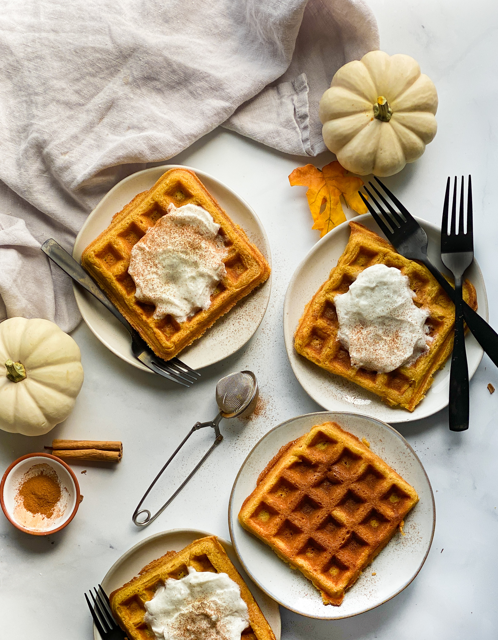 Grain-free pumpkin waffles sitting on a marble counter top on grey plates. There are four different plates and three of them have a dollop of fresh whipped cream and a dash of cinnamon on them.