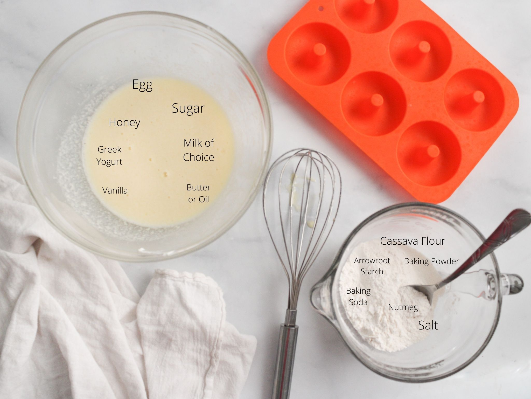 Donut ingredients in two glass bowls separated by wet and dry. One bowl has the cassava flour, arrowroot starch, baking powder, baking soda, nutmeg, and salt. The other has the egg, sugar, honey, milk, greek yogurt, butter and vanilla. The bowls are sitting next to an orange silicon donut pan.,