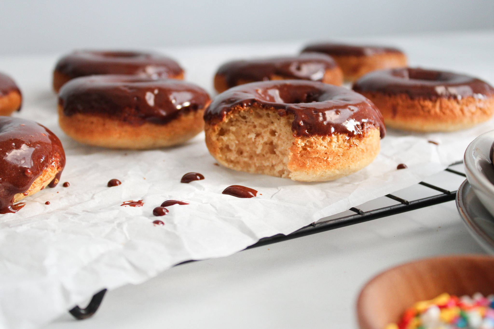 grain-free vanilla baked donuts with chocolate frosting sitting on parchment paper lined cooling rack with a bite taken out.