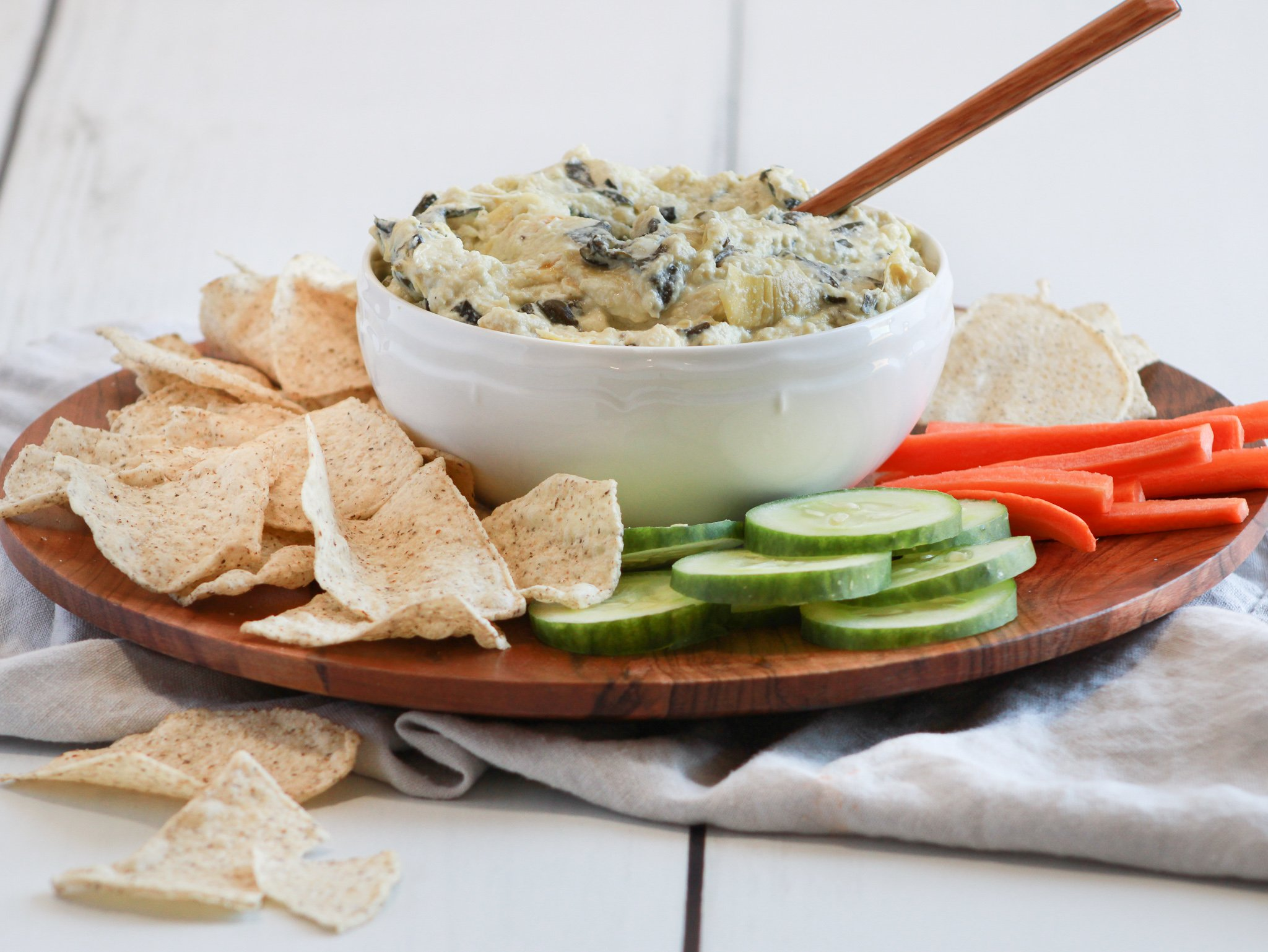 Spinach and artichoke dip in a white bowl with a wooden spoon ready to be scooped on to a chip or cucumber slice and eaten.