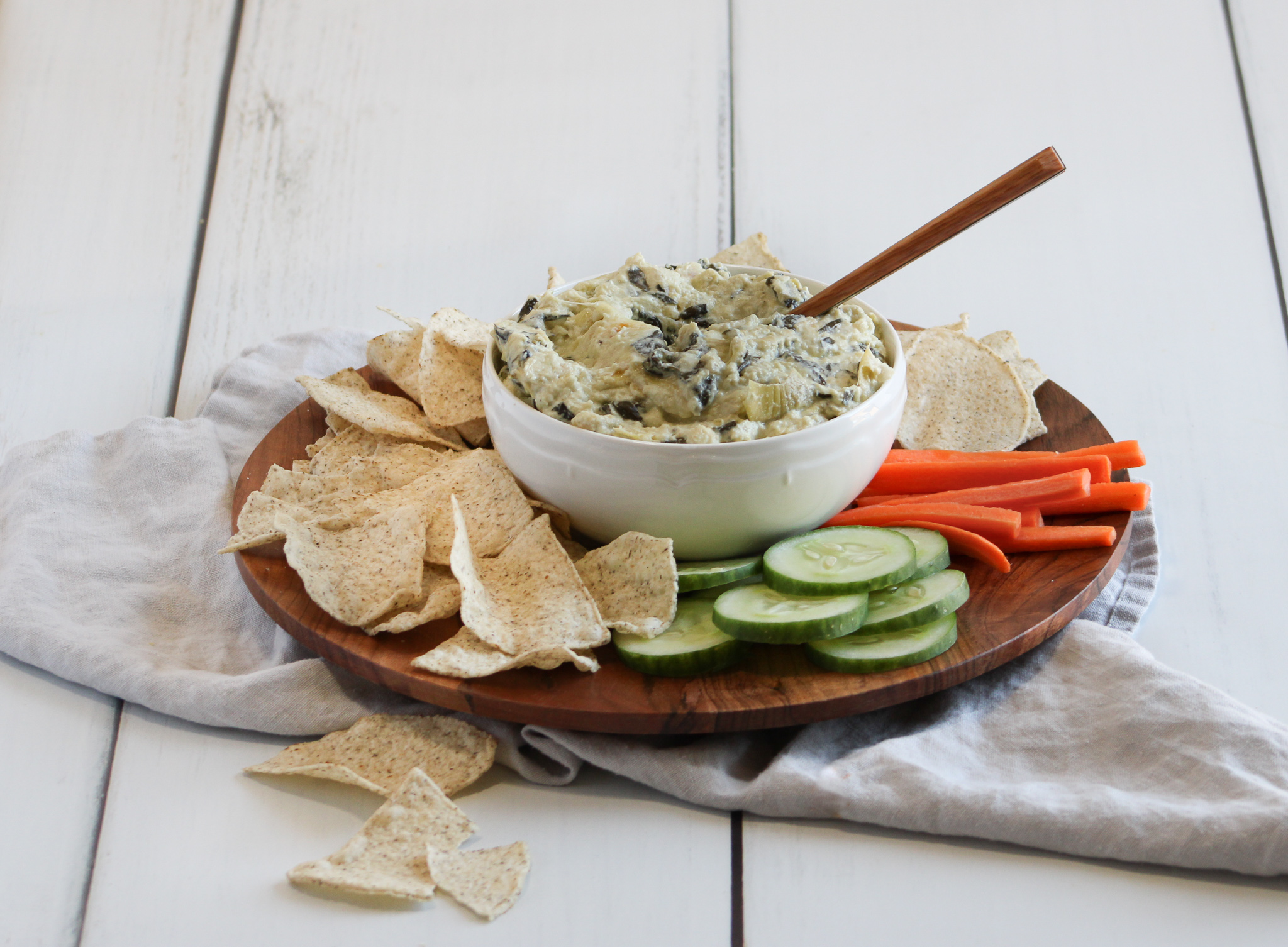 Spinach and artichoke dip sitting in a white bowl on a wooden tray surrounded by carrots, cucumber and Siete brand grain-free tortilla chips.