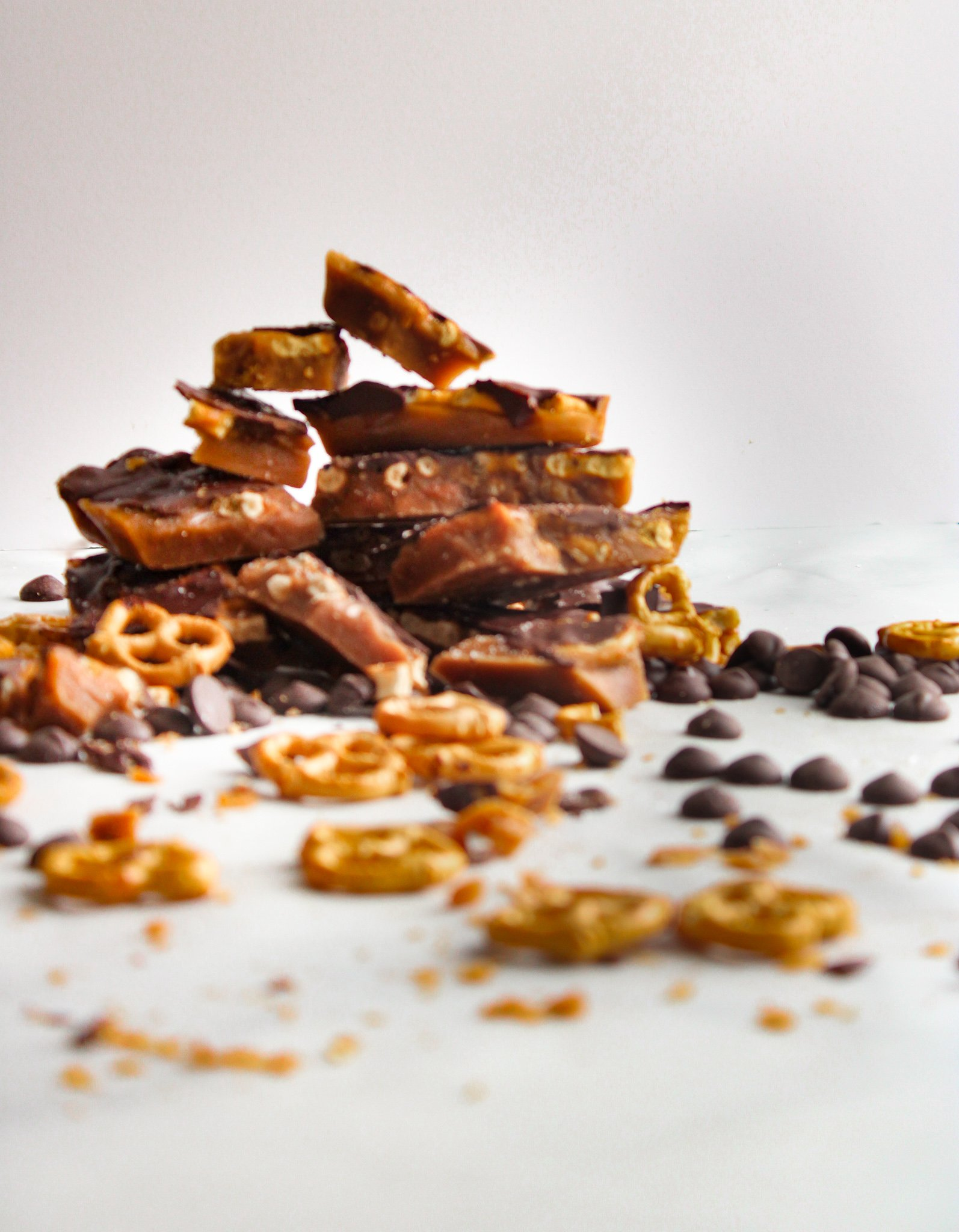 Chocolate Covered Pretzel Toffee Bark broken and in a pile stacked with scattered pretzels and chocolate chips