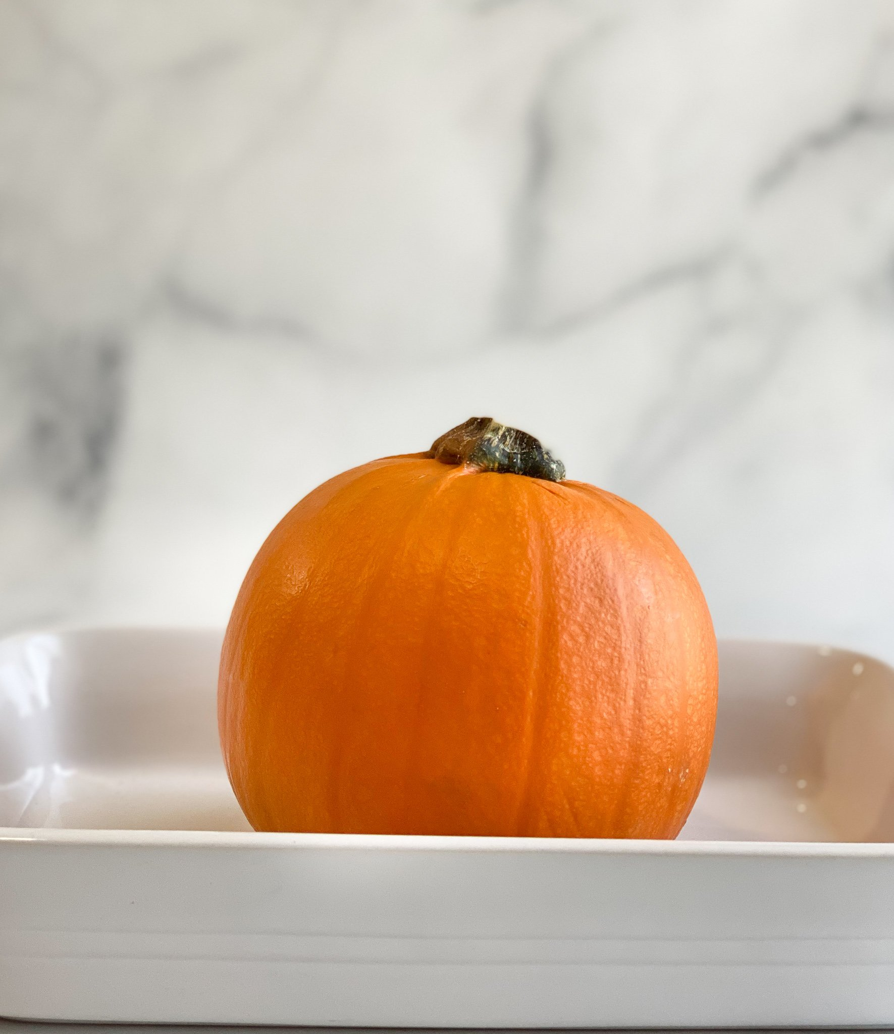 Step 2 of making pumpkin puree is to place the whole pumpkin with the cuts in the top into a shallow baking dish.