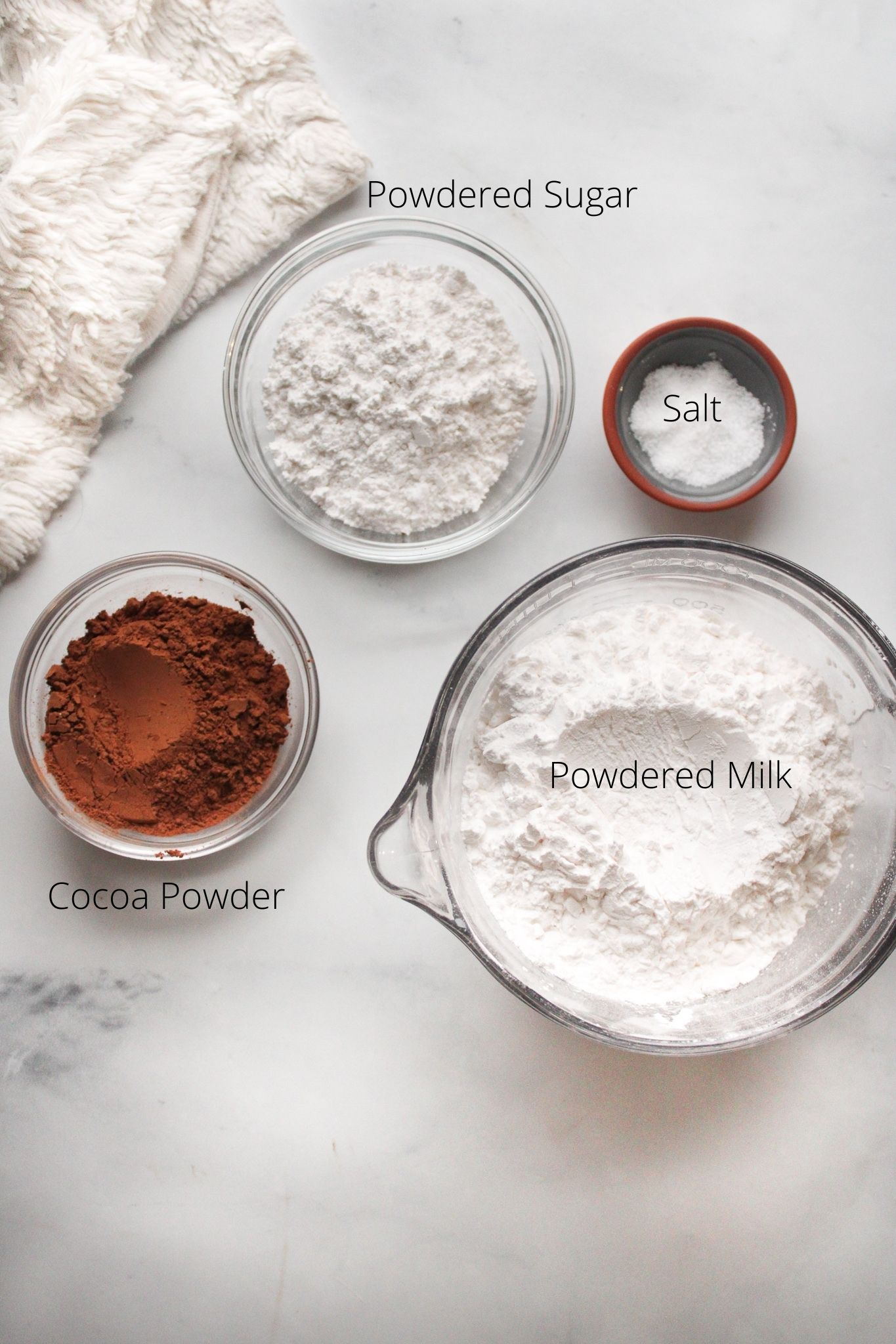 homemade hot chocolate mix ingredients powdered sugar, cocoa powder, powdered milk and salt in bowls ready to be mixed.