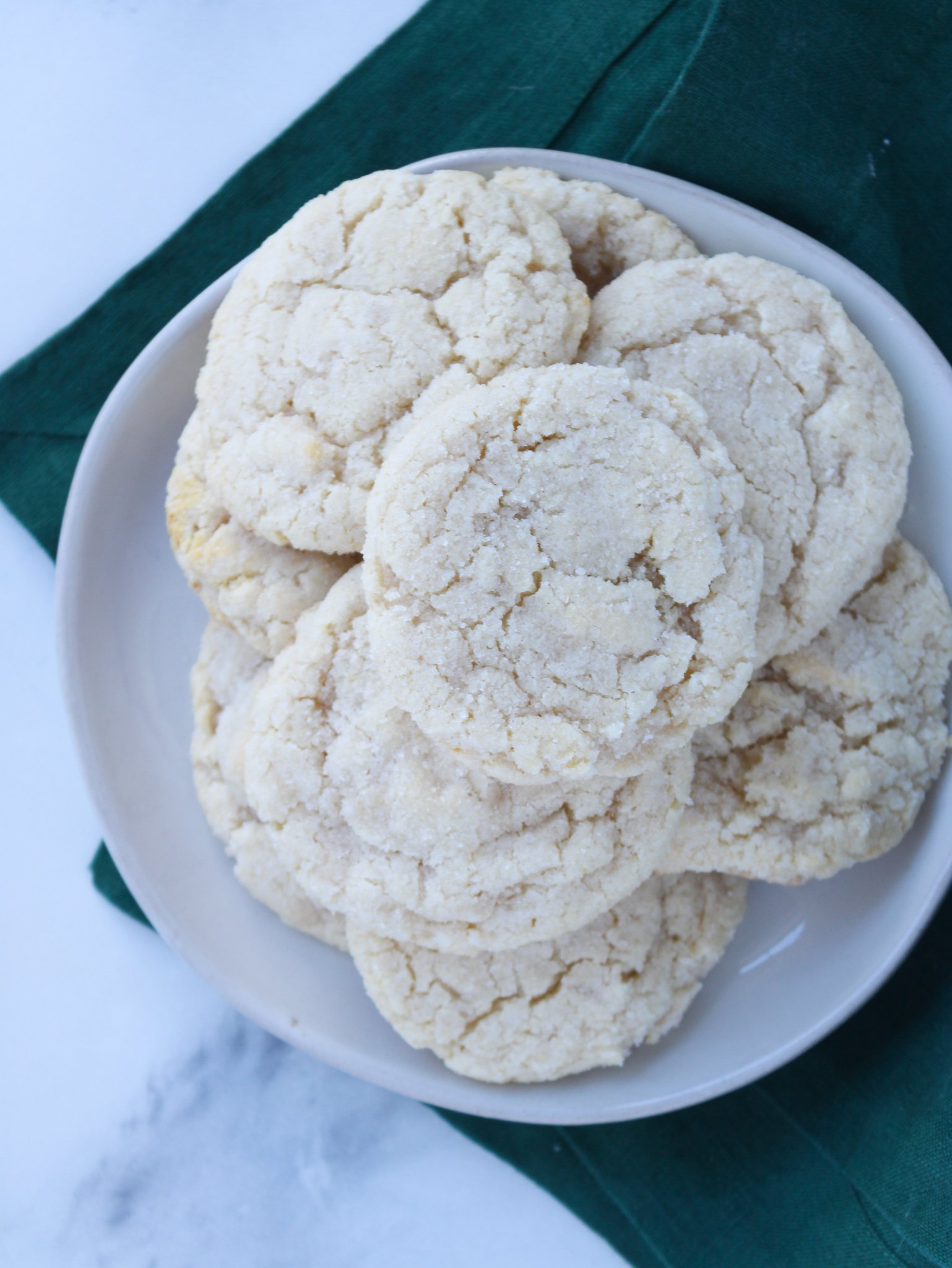 gluten free sugar cookies sitting on a grey plate over a green table linen on a marble counter