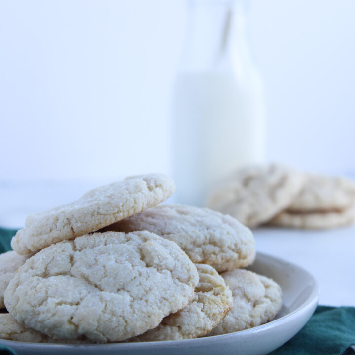 gluten free chewy sugar cookies sitting on a grey plate over a green table linen ready to be picked up and enjoyed with the glass of milk in the background