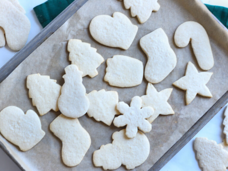 gluten free cut out sugar cookies sitting on a try hot out ofthe oven getting ready to be decorated.