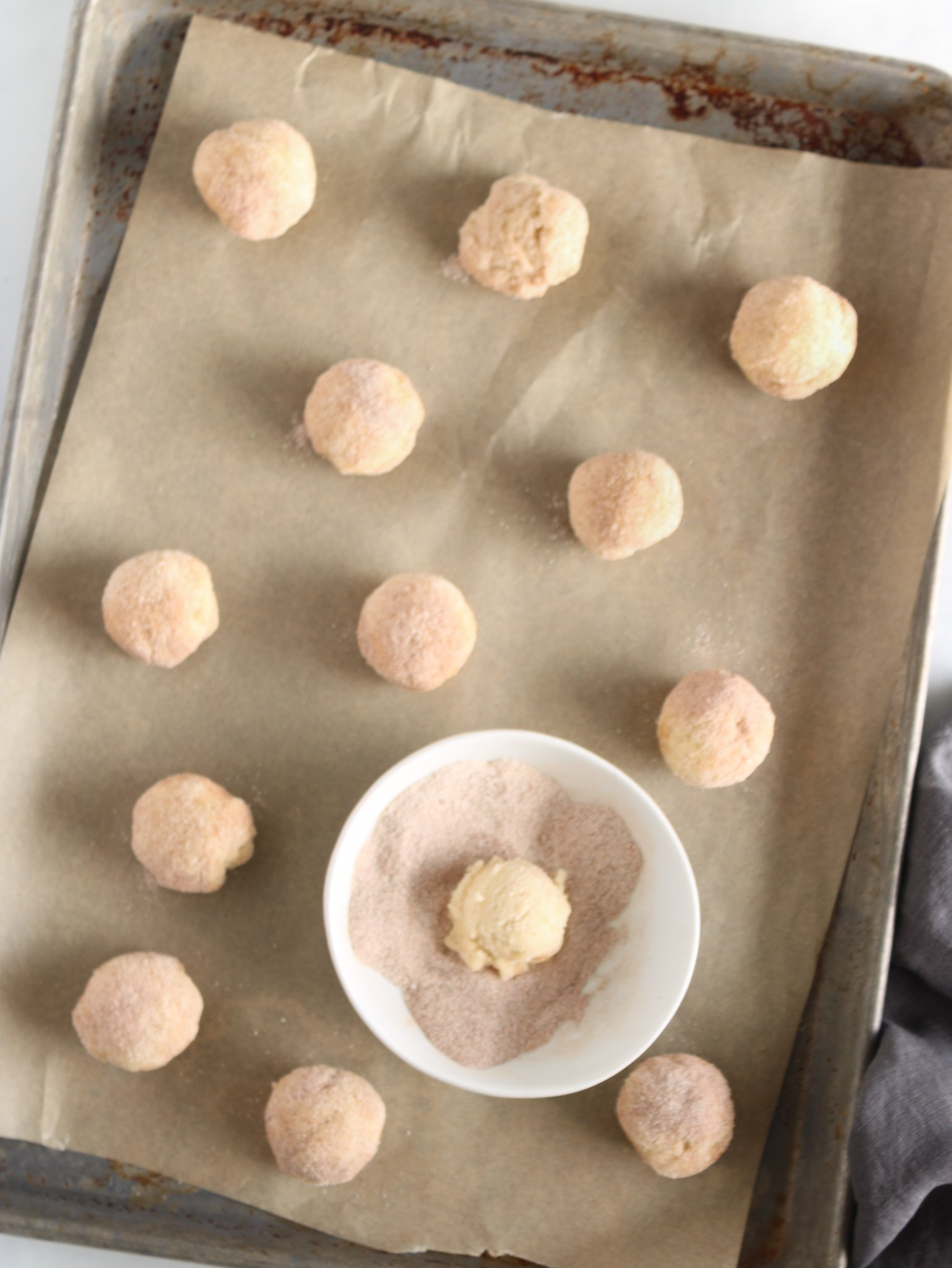 gluten free snickerdoodles on a parchment lined baking sheet being dipped into cinnamon and sugar before being baked in the oven.
