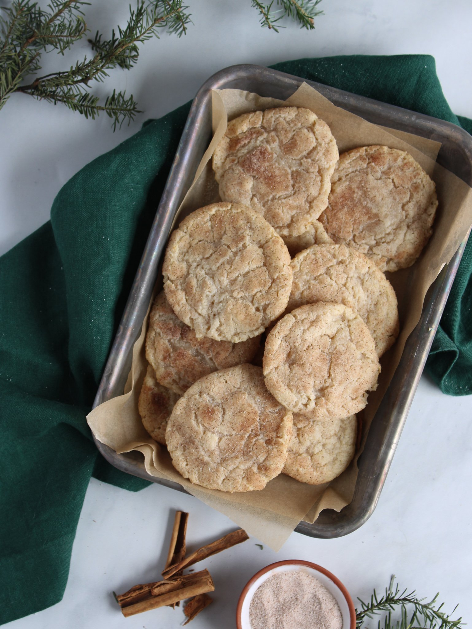 gluten free snickerdoodle cookies on a metal tray on top of unbleached parchment paper over a green linen with cinnamon sticks, cinnamon and sugar and fresh greens