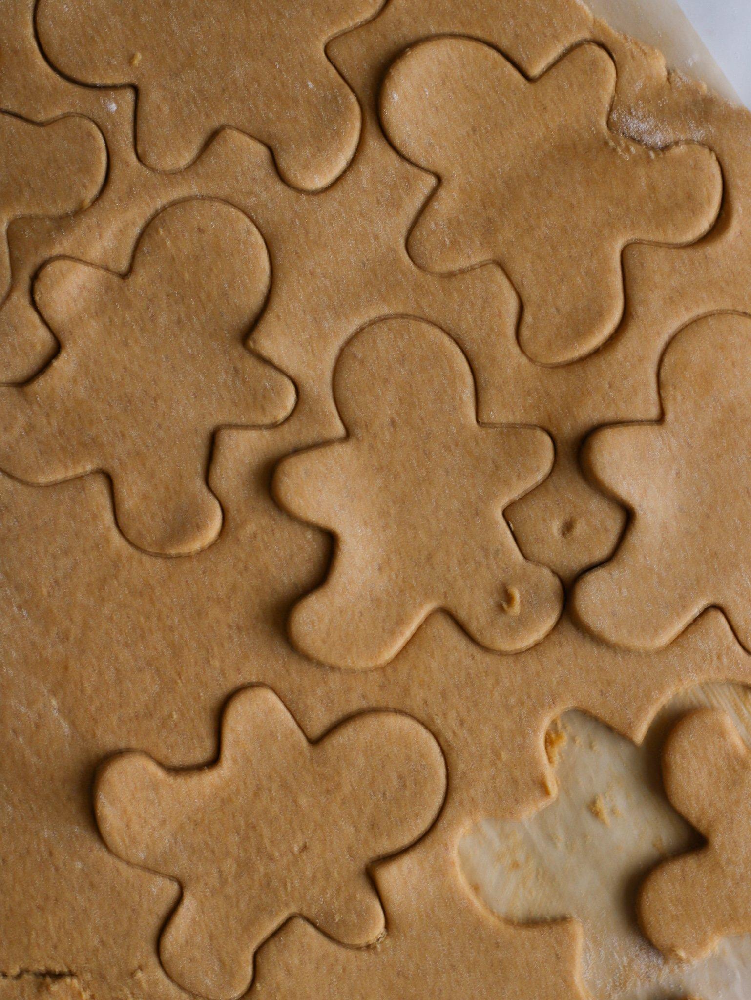 raw gluten free gingerbread cookie dough being cut into little gingerbread men