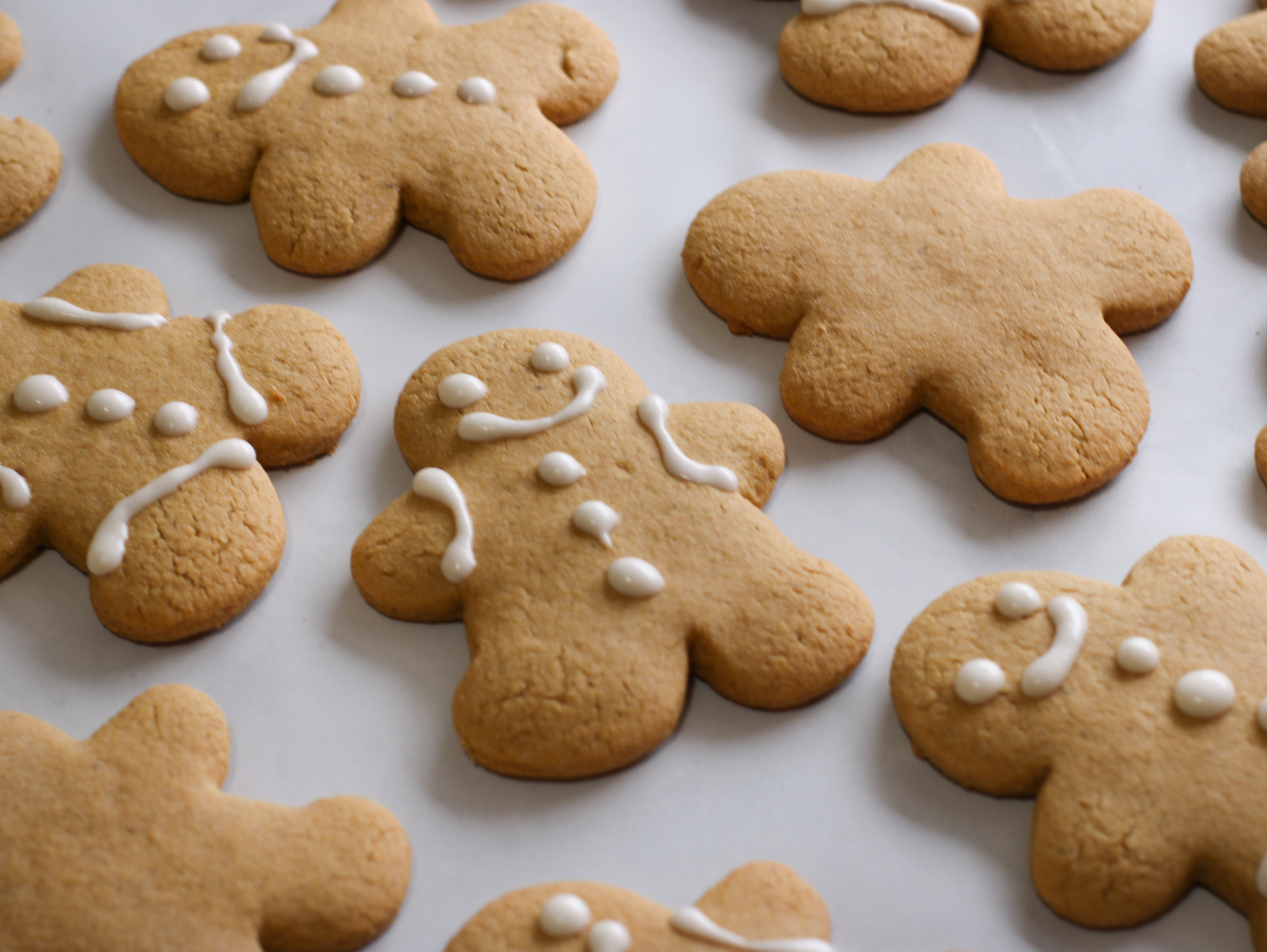 gluten free gingerbread cookies being decorated with white icing.