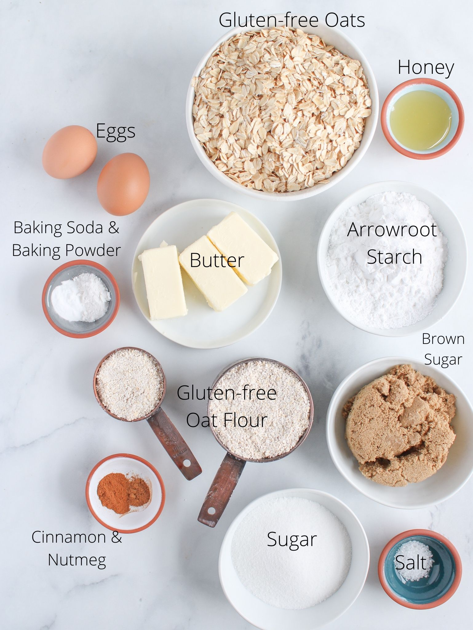 Gluten-free oatmeal cookie ingredients laid out including gluten free oats, oat flour, arrowroot starch, honey eggs, butter, sugar, brown sugar, baking soda, baking powder, cinnamon, nutmeg and salt.