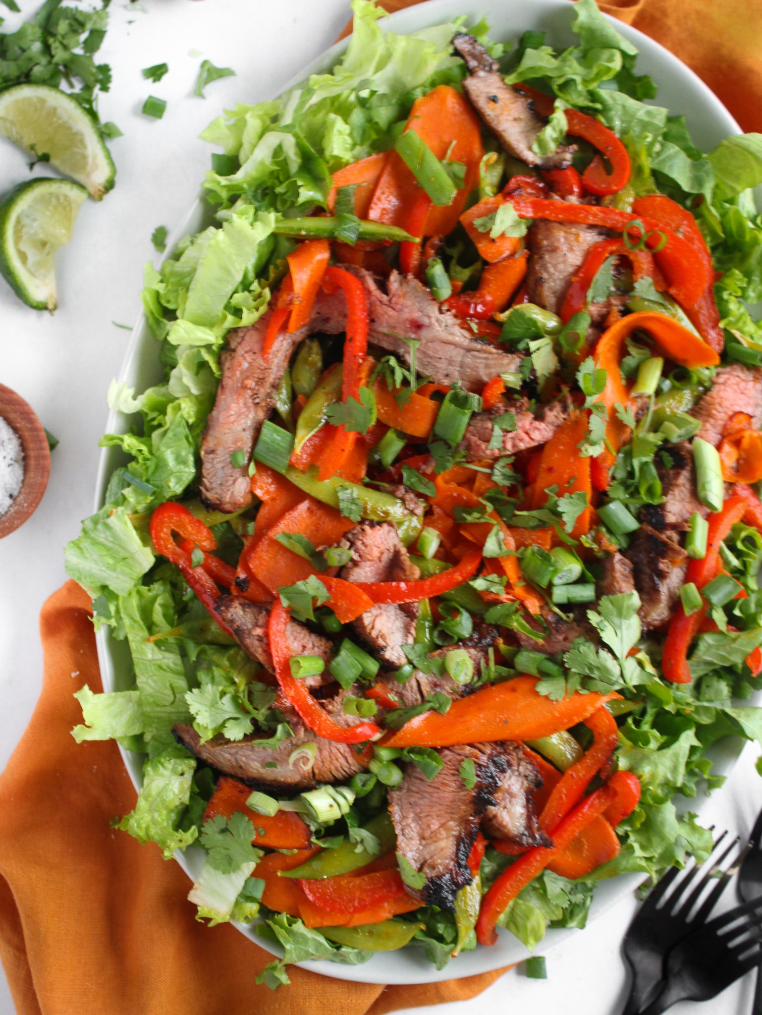 Grilled Asian Steak and Veggies salad on a white platter over a burnt orange table linen ready to be enjoyed for lunch or an easy dinner.