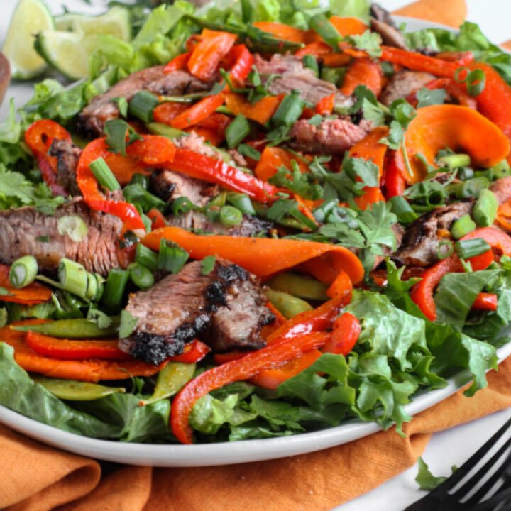 Asian grilled steak salad and veggies on a white platter over a burnt orange table linen and black forks ready to be enjoyed.