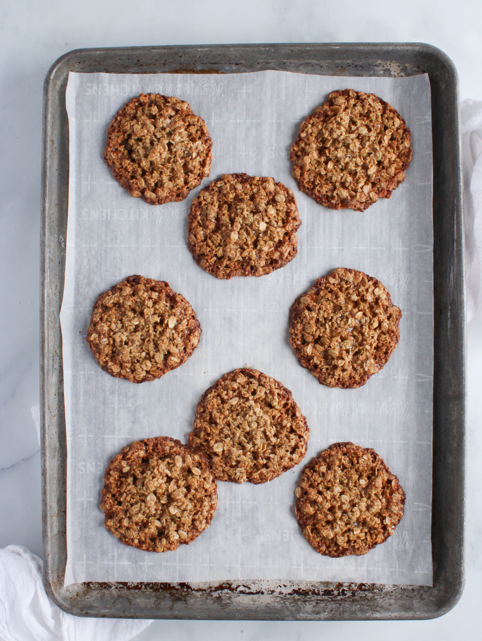 gluten free oatmeal cookies baked and cooling on a baking sheet lined with parchment paper