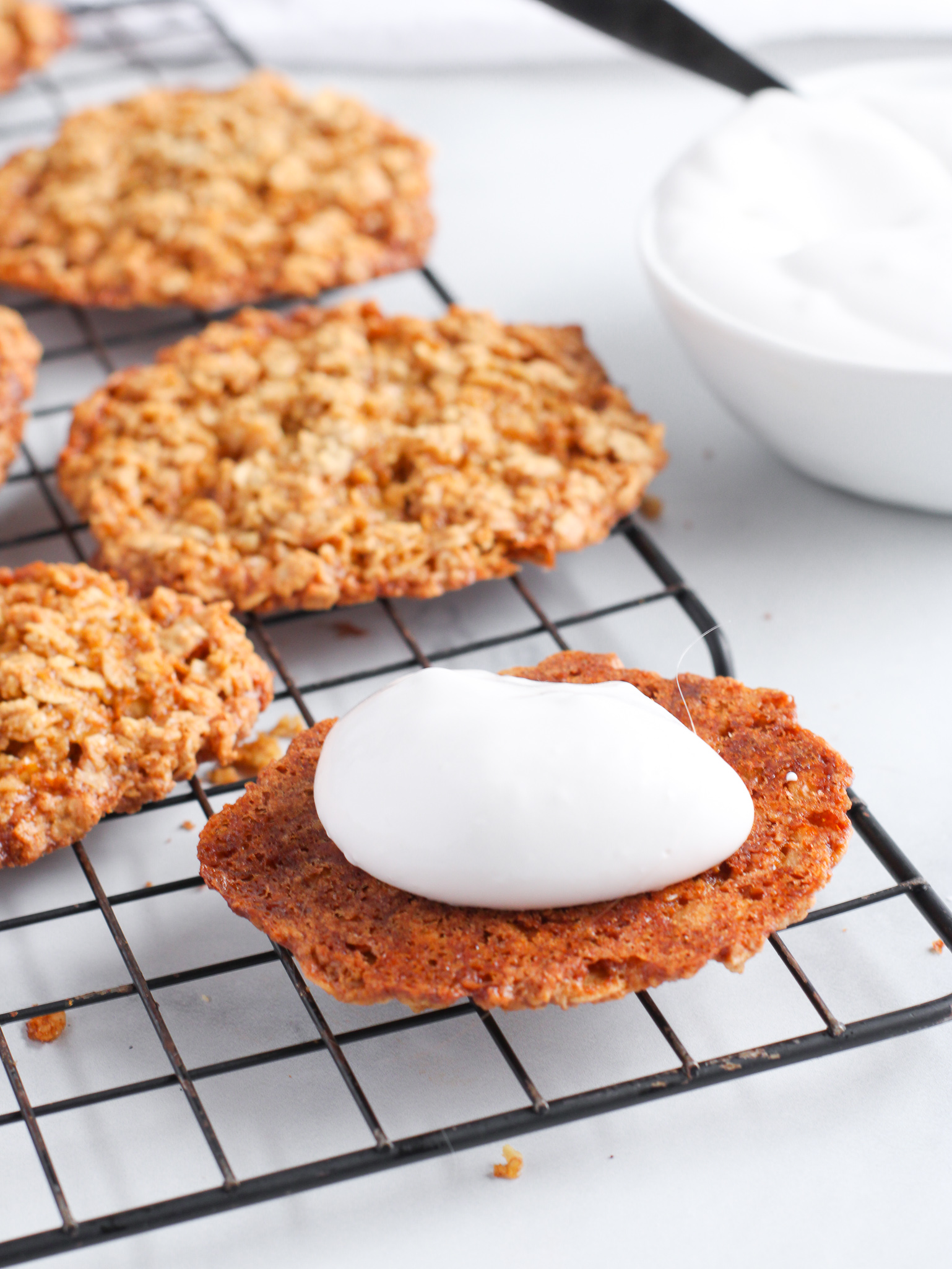 gluten free oatmeal cream pies being assembled with the cookies and a dollop of cream filling ready for the top cookie to make the sandwich.
